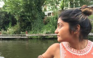 Aditi, a young person with dark hair and blonde highlights in their bun, sits in front of water with green trees in the background. They are turned in profile and are wearing an orange tank top with white patterned embroidery.