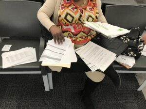 A woman in a square patterned shirt sits in an administrative office with dozens of documents spread across her lap and the chairs next to her