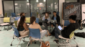 A group of people sit around in a circle with laptops open in their laps. Behind them is a chalkboard that says