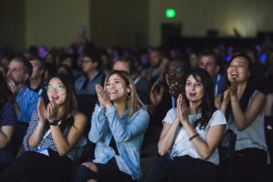 A group of people in the audience at Summit 2019 applauding