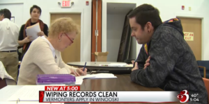 a local news feature of the expungement clinic. two people sit across from each other at a table filling out paperwork