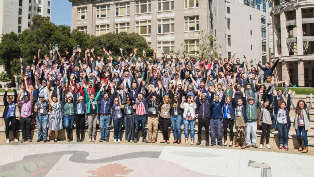Group photo of Brigade members attending Summit 2019. They wave their hands in the air with trees and buildings in the background.